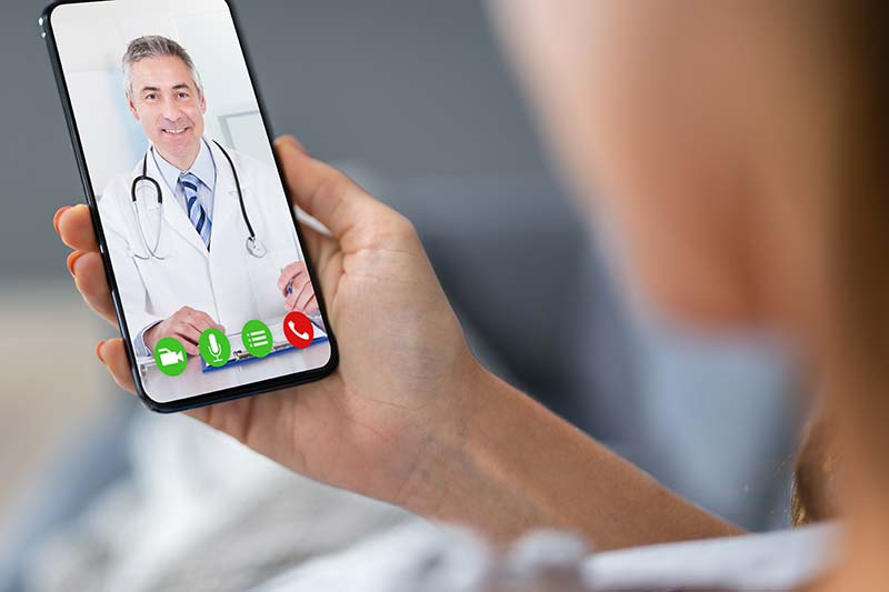 A closely cropped photo of a person videochatting with a doctor using a mobile phone.