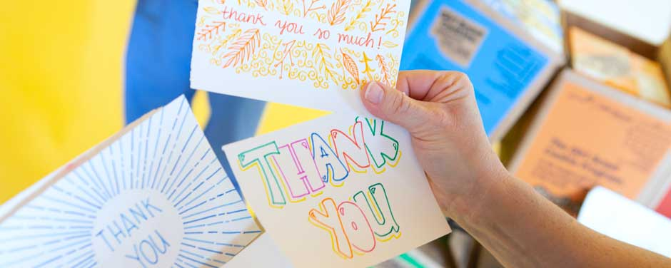 Someone holding up handwritten thank you cards