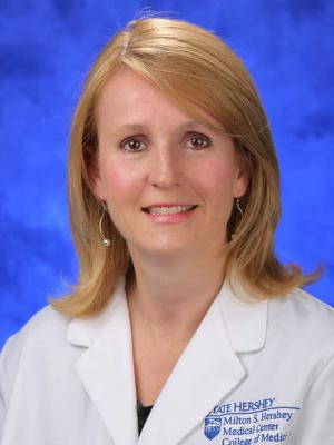 A professional head and shoulders photo of Dr. Sarah Iriana. She is wearing a white medical jacket.