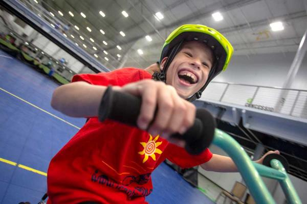 Young CMN child riding his bike indoors