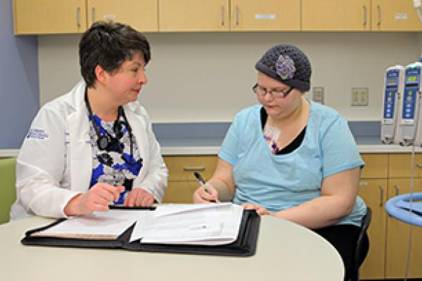 A Penn State researcher helps a clinical trial patient.