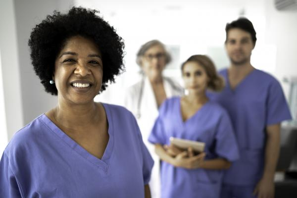 One nurse smiles at the camera while three other nurses stand behind them.