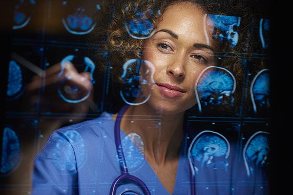 a female doctor or surgeon is analyzing the digitally generated scans  of a human brain.