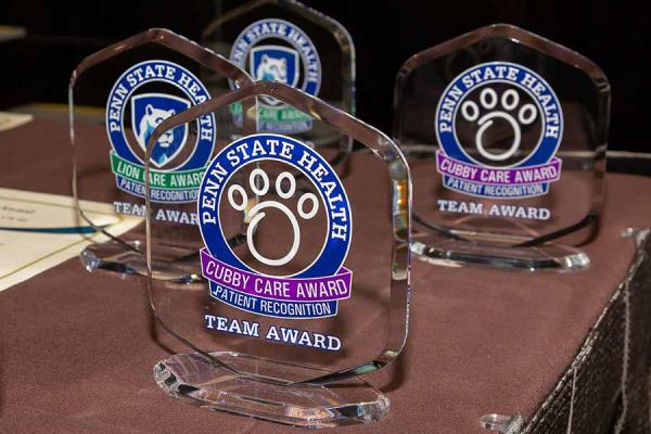 Penn State Health Cubby Care and Lion Care Awards are displayed on a table top