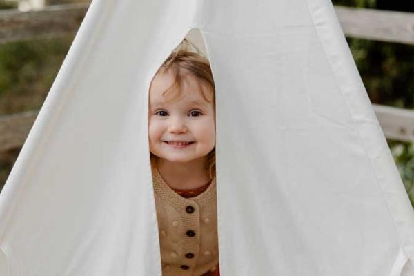 Happy little child smiling while peeking from tent.
