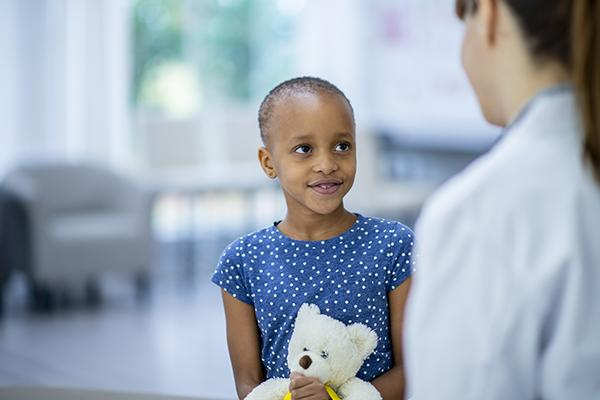 A female doctor and cancer patient are indoors in a hospital room. The girl is smiling while holding a teddy bear. The doctor is telling the girl about her checkup.