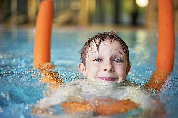 Happy kid learning to swim in indoors swimming pool. The boy is aged 5  and is using orange pool noodle. He is smiling into the camera.