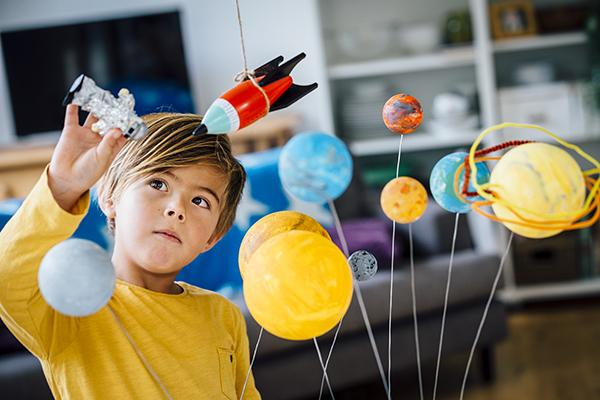 Little boy playing with his homemade planetarium as he holds an astronaut. A rocket hangs above. Arms raised as he plays.
