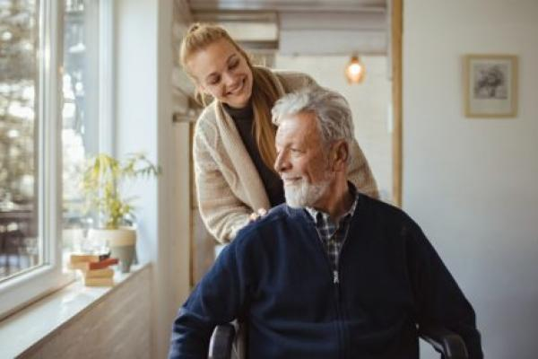 A woman pushes an older man in a wheelchair, as both smile. They are next to a sunny window.