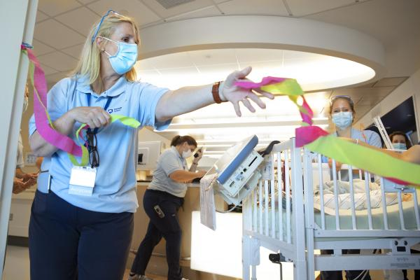 Dr. Sarah Iriana extends her arm holding a handful of ribbon next to a crib. Equipment is draped from the side of the crib. Behind her, three women in surgical masks look on or focus on other work.