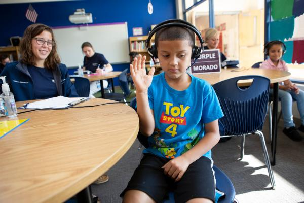 A boy wearing headphones raises his arm while doing a hearing test