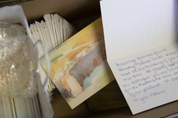Stacks of cards sit in a cardboard box. The front of the card shows a watercolor painting of Hershey Medical Center. One card is propped open to show handwriting inside.
