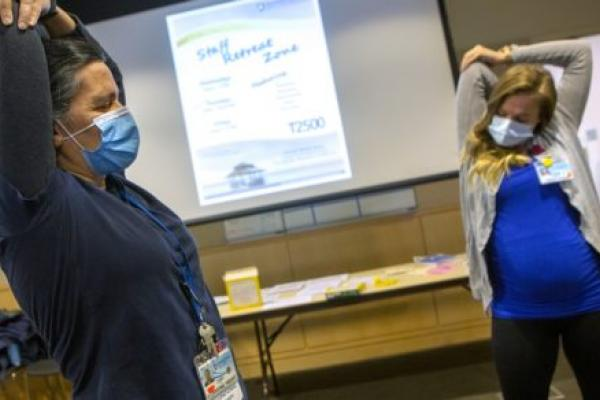 "Two women wearing surgical masks and lanyards with nametags pull their elbows as they stretch their arms. A slide with the words ""Staff Retreat Zone"" is on a screen between them. A table is in the background."