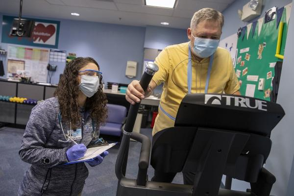 Woman in grey Penn State Health jacket wearing safety glasses, facemask and gloves, writes on a clipboard as a man in a yellow shirt wearing a face mask walks on an exercise machine during an in-person cardiac rehabilitation visit.