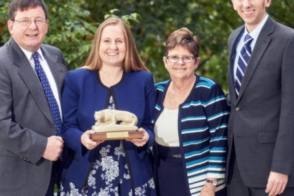 Kristin Lambert is seen standing with her family outdoors. She is holding a small statue of the Penn State Nittany Lion.