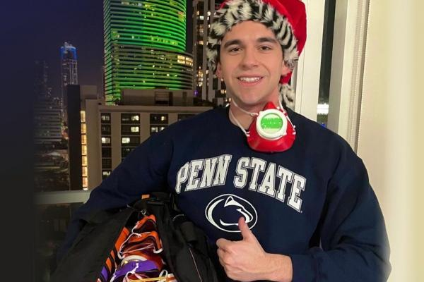 First-year College of Medicine medical student Marc Levine stands in front of a window at night wearing a Penn State T-shirt and Santa cap. He is giving the thumbs up and smiling. He has a face mask hanging from his neck and is holding a large bag with ma