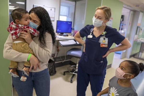 Terianny Vicente holds son Calvin, who is wearing a plaid shirt and pants, as Jo Rosenberger and Calvin's big sister look on. Vicente, who has long hair, wears a sweater, jeans and a mask. Rosenberger wears scrubs and a mask. Hospital equipment and comp