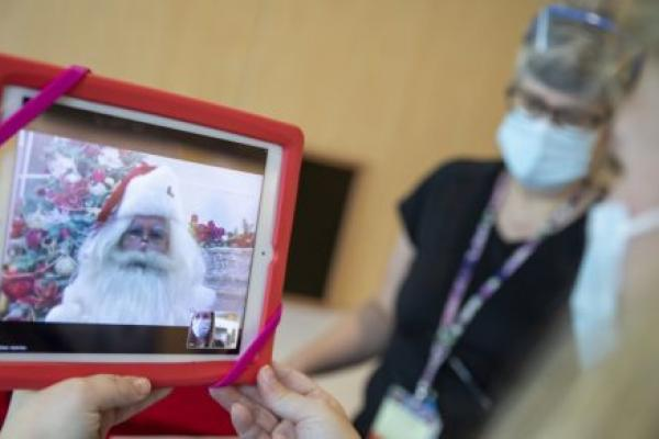 A woman holds a notepad, upon which is a view of Santa Claus's face. Next to her is another woman in personal protective equipment.
