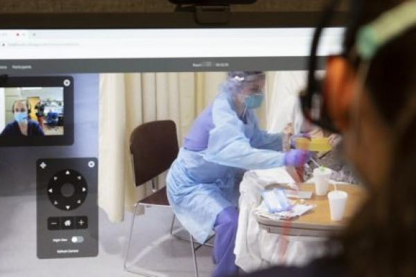 Image shows over the shoulder someone looking at a computer monitor. In one window on the monitor is the view of someone in a mask. To the right, someone in personal protective equipment works with a patient.