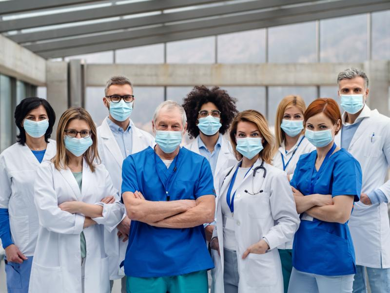 A group of healthcare professionals in masks look into the camera.