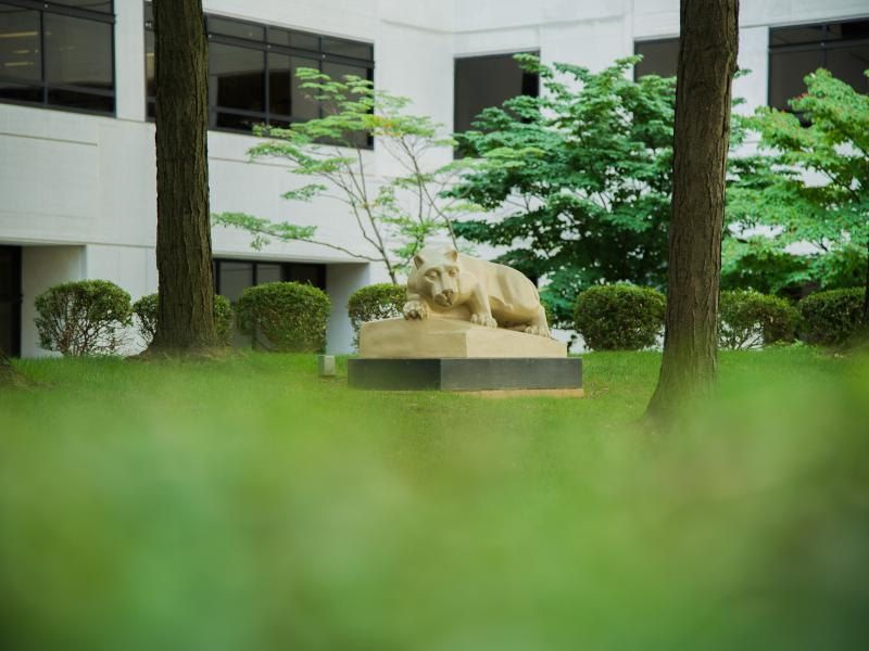 A nittany lion statue surrounded by greenery.
