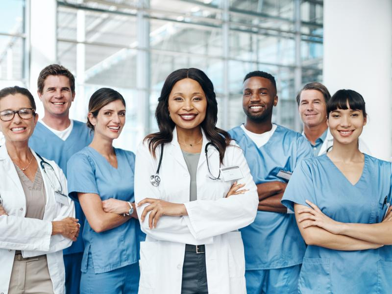 A group of health care professionals smile at the camera.