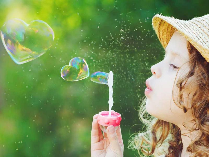 Young girl blowing heart bubbles