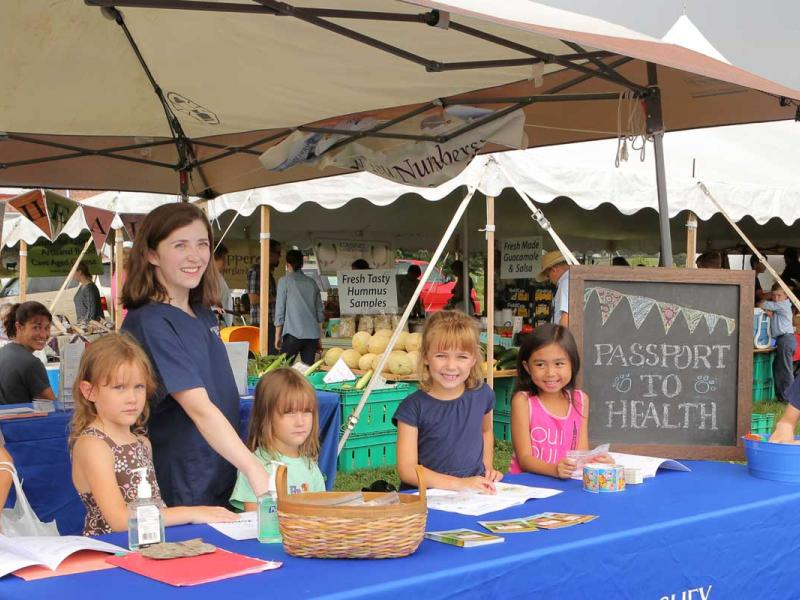 A group of children standing behind a table at a farmer's market.