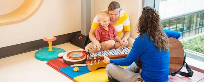 A caregiver does music therapy with a patient and his mother.
